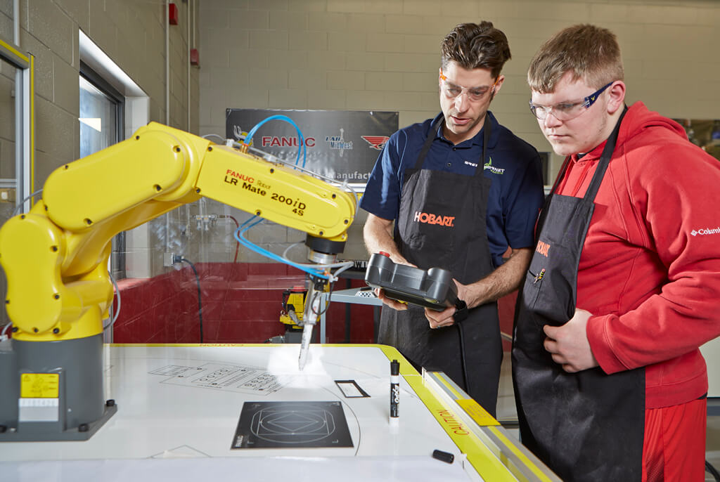 Two males working with a robotic arm