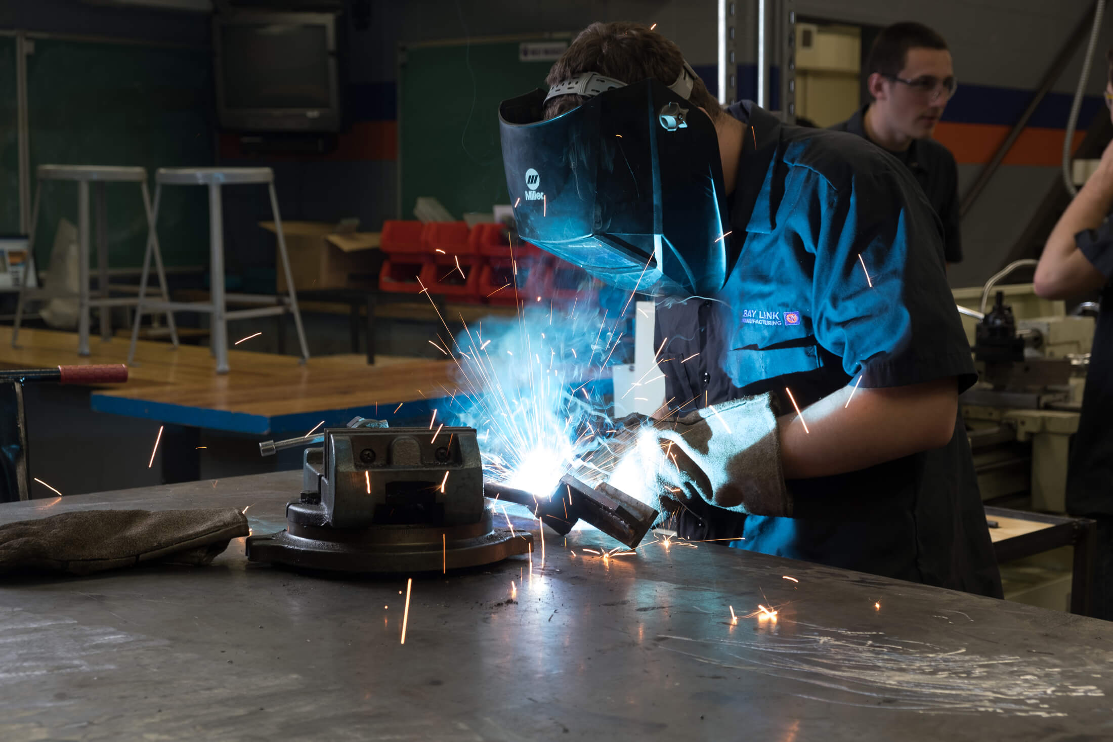 Person in blue welding with white glow