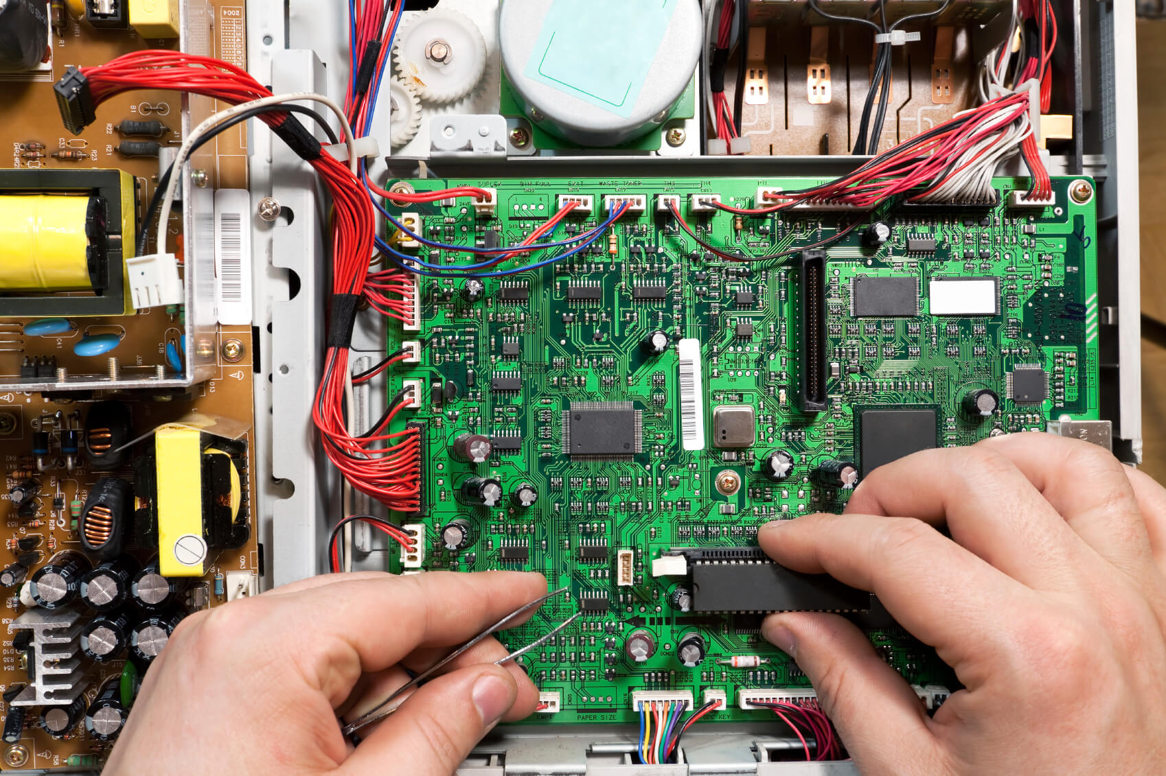 Green circuit board with two hands.